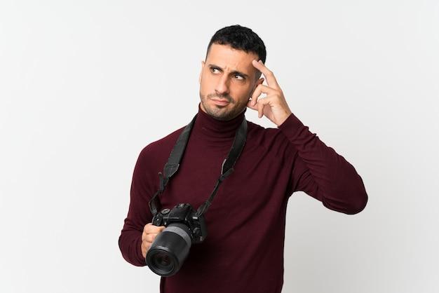 Giovane sopra bianco isolato con una macchina fotografica e un pensiero professionali