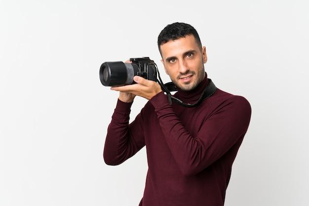 Giovane sopra bianco isolato con una macchina fotografica professionale