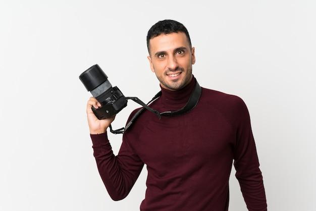 Giovane sopra fondo bianco isolato con una macchina fotografica professionale