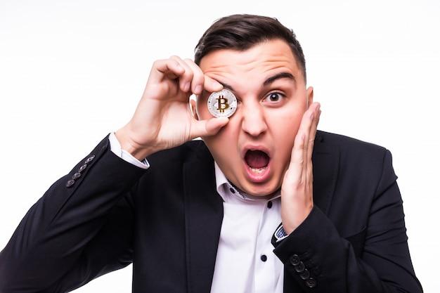 Giovane sorpreso su bianco tiene la moneta bitcoin nelle sue mani