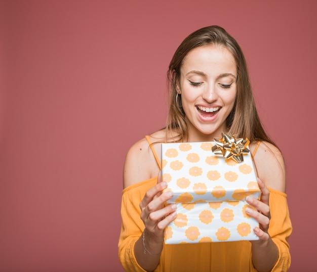 Giovane sorridente che apre il contenitore di regalo floreale con l'arco dorato