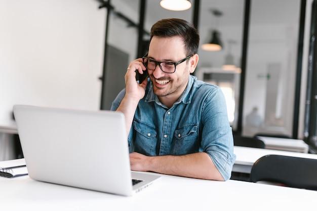 Giovane sorridente che parla sullo smartphone mentre sedendosi davanti al computer portatile.