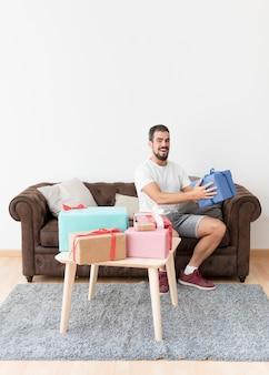 Giovane sorridente che si siede sul sofà che tiene il contenitore di regalo blu a casa