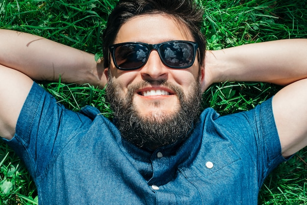 Giovane sorridente che si trova e che si distende sull'erba verde