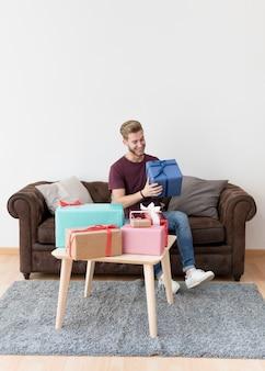 Giovane sorridente che tiene scatola attuale che si siede sul sofà a casa