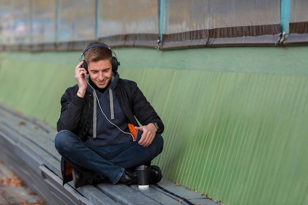 Giovane sorridente dello smiley che ascolta la musica sulle cuffie su un banco
