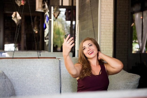 Giovane sorridente felice bello plus size modella che fa selfie, donna xxl in un caffè.