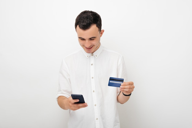 Giovane sorridente nel bianco su bianco che esamina il telefono e che tiene la sua carta di credito. mobile banking e concetto di shopping online.