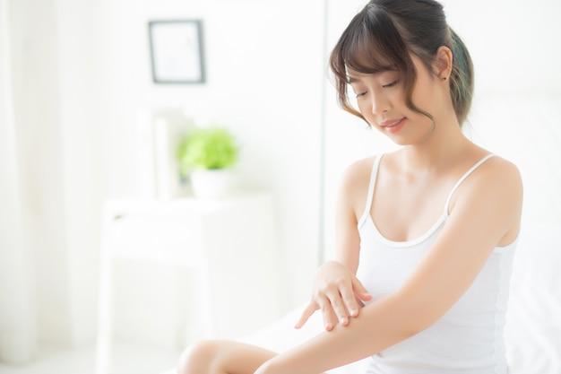 Giovane sorriso asiatico della donna del bello ritratto che applica la crema della protezione solare