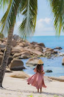 Giovane sorriso asiatico della donna del ritratto felice intorno all'oceano del mare della spiaggia con l'albero del cocco per la vacanza di festa