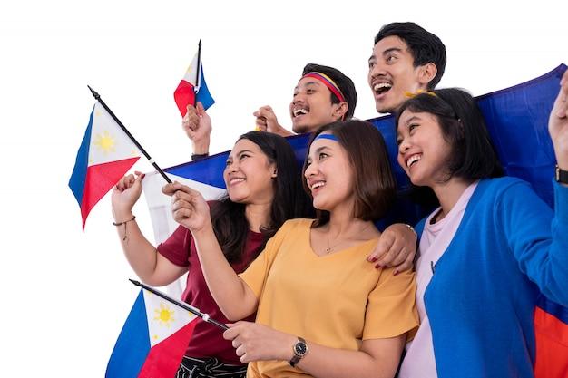 Giovane sostenitore asiatico emozionante che tiene la bandiera delle filippine