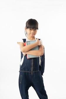 Giovane sovraccarico asiatico del libro della tenuta della studentessa isolato su fondo, su istruzione e sull'apprendimento bianchi