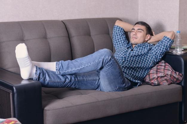 Giovane spensierato rilassato sul divano con le mani dietro la testa, sognando il futuro