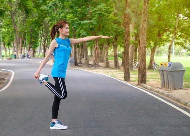 Giovane sportiva asiatica che si estende e si prepara a correre al parco