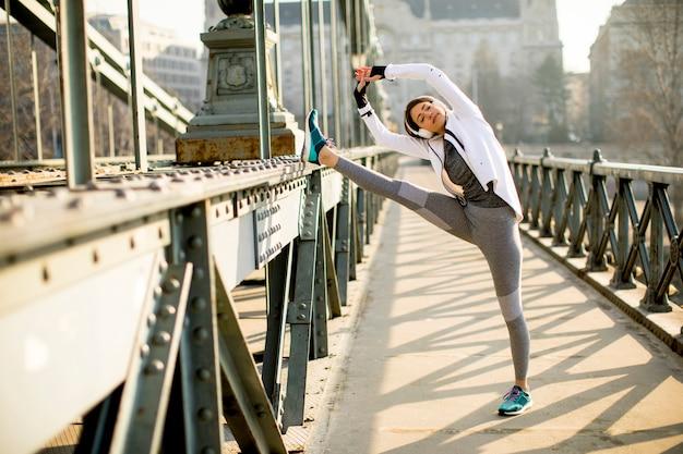 Giovane sportiva che si estende e si prepara a correre