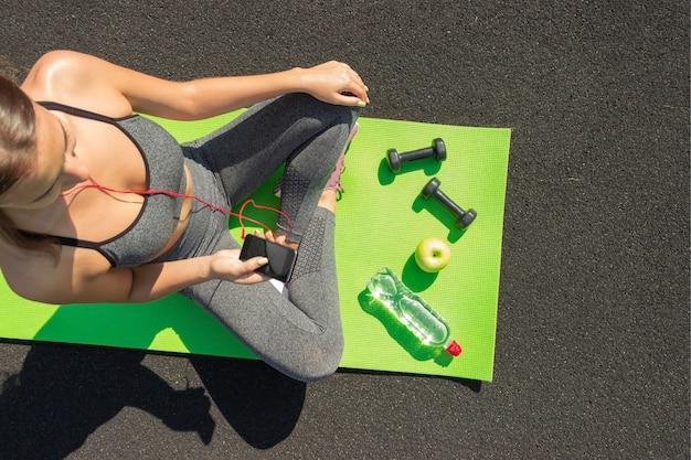 Giovane sportiva di forma fisica che si siede e che utilizza smartphone nella palestra.