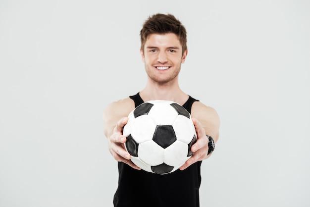 Giovane sportivo allegro con la sfera di piede