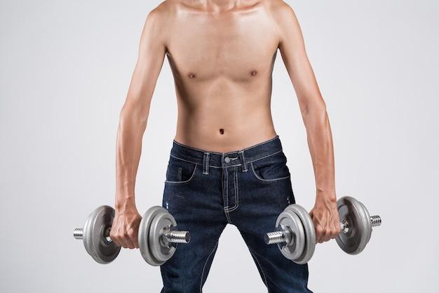 Giovane sportivo asiatico sottile che risolve con i pesi di ginnastica e di ligting