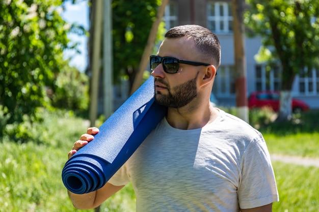 Giovane sportivo barbuto che tiene una stuoia blu al parco. esercizio di pratica di forma fisica di yoga del giovane all'aperto.