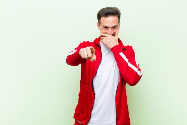 Giovane sportivo bello uomo o monitor ridere di te, indicando la fotocamera e prendendo in giro o deridendoti contro la parete piatta