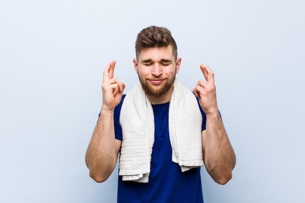 Giovane sportivo caucasico con le dita dell'incrocio di un asciugamano per avere fortuna
