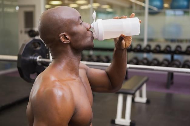 Giovane sportivo che beve proteina in palestra