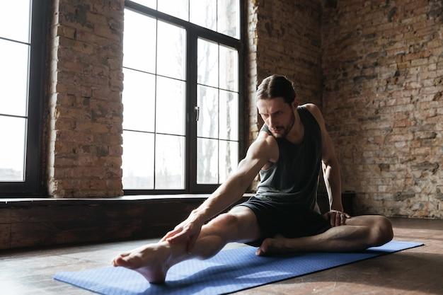 Giovane sportivo concentrato che allunga i muscoli sulla stuoia di forma fisica