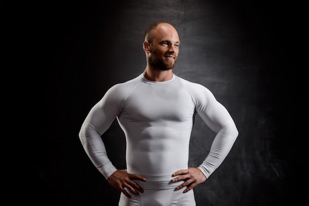Giovane sportivo potente in abiti bianchi sul muro nero.
