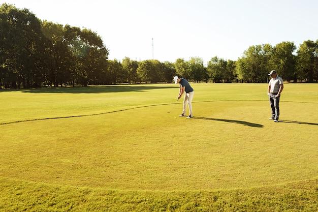Giovane sportivo praticare il golf con il suo insegnante