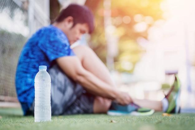 Giovane sportivo rilassante dopo la mattina calda raggi di luce, bottiglia d'acqua