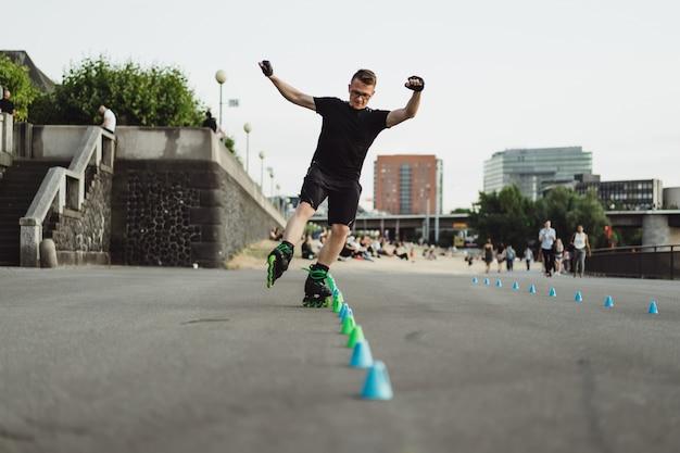 Giovane sportivo uomo su pattini a rotelle in una città europea. sport in ambienti urbani.
