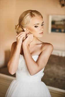 Giovane sposa bella e alla moda, ragazza modello bionda sexy con gli occhi azzurri e acconciatura alla moda in abito bianco regolando l'orecchino e in posa all'interno, preparazione del matrimonio al mattino