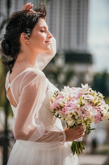 Giovane sposa castana in un vestito bianco con il mazzo. ritratto del primo piano di una donna all'aperto