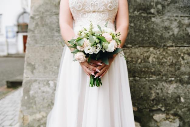 Giovane sposa caucasica che tiene il suo mazzo di nozze davanti lei il giorno delle nozze