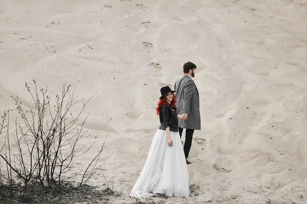 Giovane sposa in abito bianco, giacca di pelle nera e cappello a seguito di giovane sposo bello e guardando indietro verso la telecamera. coppia felice di sposini in posa nel deserto. concetto di amore e matrimonio