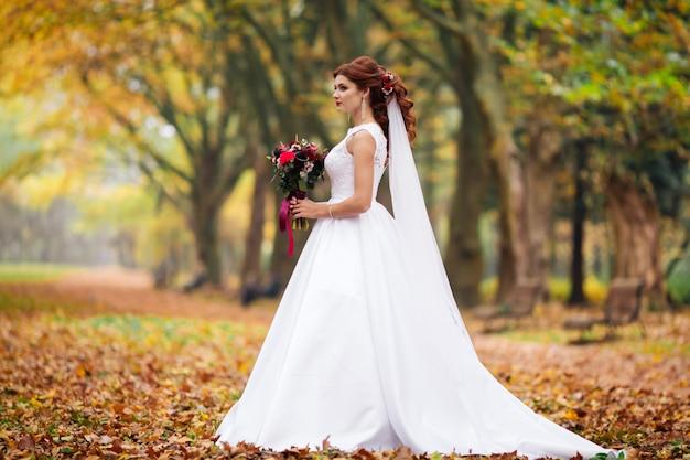 Giovane sposa in abito da sposa che cammina in un parco. abito bianco di lusso per donna. la sposa cammina nel parco.