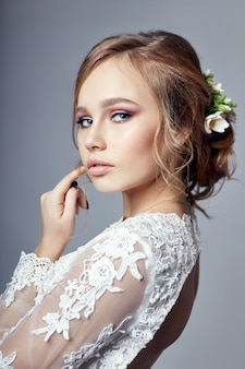 Giovane sposa in un lussuoso abito da sposa bianco