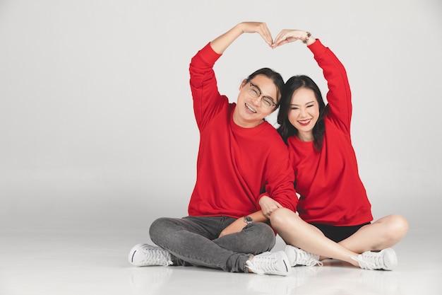 Giovane sposo e sposa asiatici che posano e che sorridono per il pre-matrimonio.