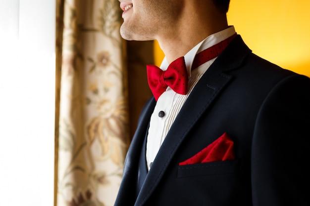 Giovane sposo in abito blu scuro con papillon rosso punteggiato e fazzoletto in tasca