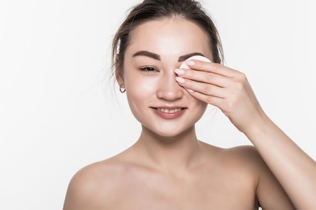 Giovane spugna asiatica attraente di uso di bellezza della donna isolata sulla parete bianca
