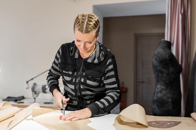 Giovane stampino sorridente di forbici del sarto per la fabbricazione dei vestiti