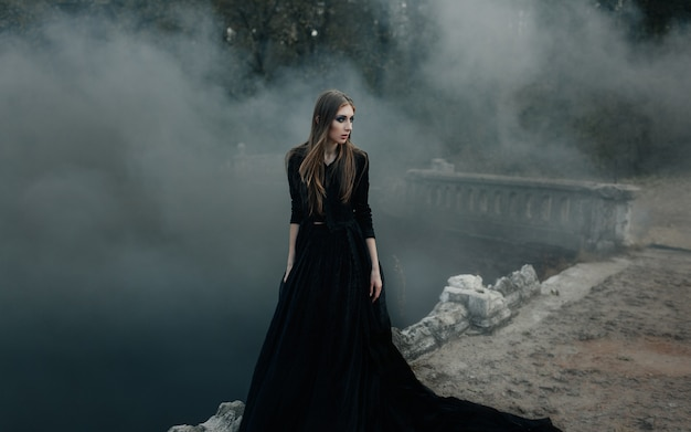 Giovane strega attraente che cammina sul ponte in fumo nero pesante.
