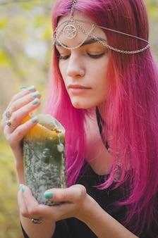 Giovane strega con i capelli rosa che esegue un rituale magico con una grande candela verde, colori sbiaditi, messa a fuoco selezionata