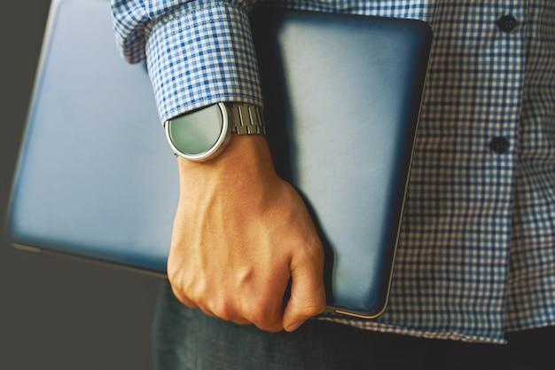 Giovane studente adulto in una camicia con uno smartwatch che tiene un computer portatile