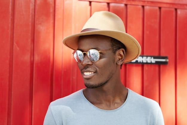Giovane studente africano allegro in cappelleria alla moda ed occhiali che distolgono lo sguardo e che sorridono felicemente