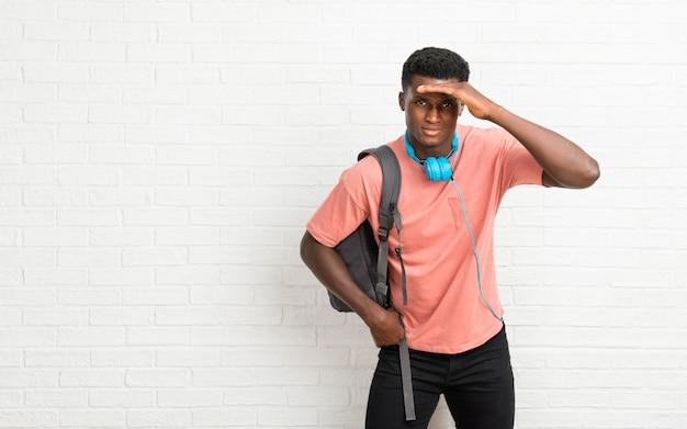 Giovane studente afro americano uomo guardando lontano con la mano per guardare qualcosa