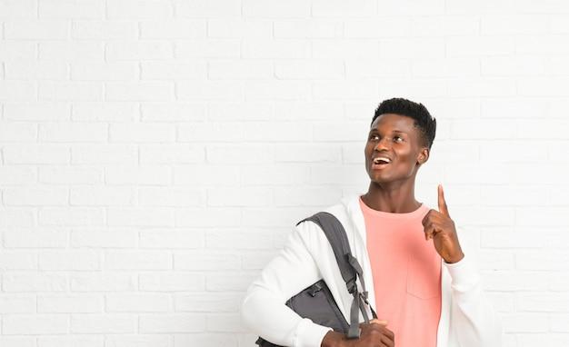 Giovane studente afro americano uomo in piedi e pensando un'idea che punta il dito verso l'alto