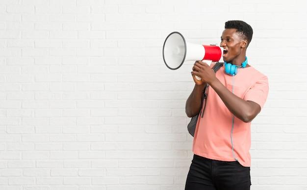 Giovane studente afro americano uomo in possesso di un megafono