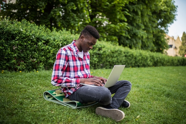 Giovane studente afroamericano che si siede sull'erba con il computer portatile vicino al campus