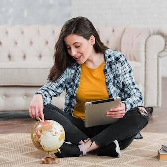 Giovane studente astuto che per mezzo di un globo del mondo